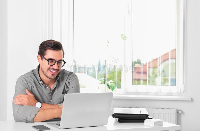 Handsome young man working with  at table in office royalty free stock image