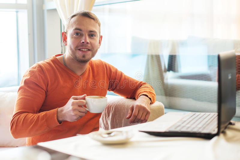 Handsome young man working on notebook, smiling, looking at camera, while enjoying coffee in cafe royalty free stock photography