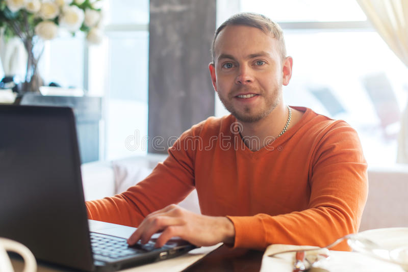 Handsome young man working on notebook, smiling, looking at camera, while enjoying coffee in cafe stock photos