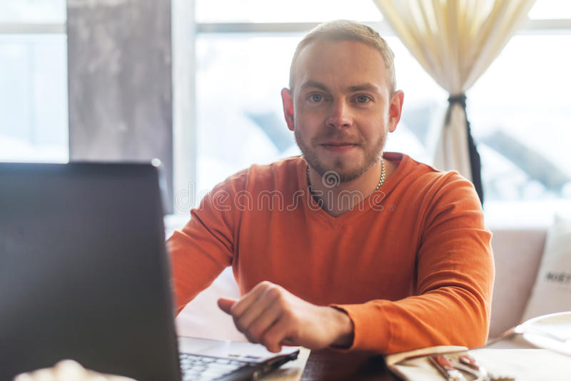 Handsome young man working on notebook, smiling, looking at camera, while enjoying coffee in cafe royalty free stock image