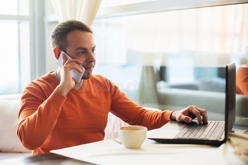 Handsome young man working with notebook, talking on the phone, smiling, while enjoying coffee in cafe royalty free stock photography