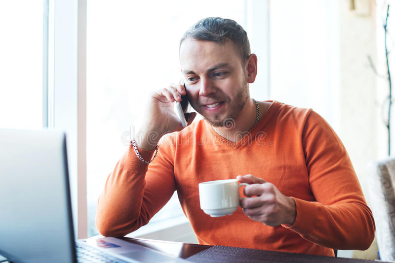 Handsome young man working with notebook, talking on the phone, smiling, while enjoying coffee in cafe royalty free stock image