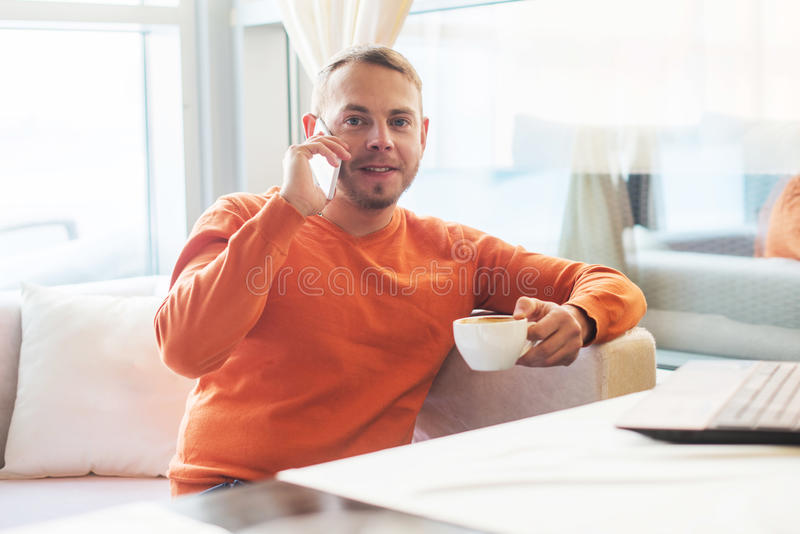 Handsome young man working with notebook, talking on the phone, smiling, looking at camera, while enjoying coffee in cafe royalty free stock image