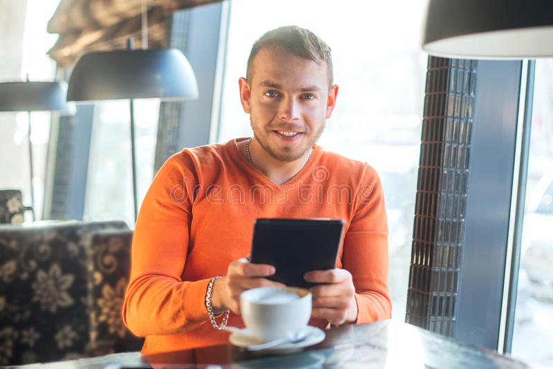 Handsome young man working with tablet, looking at camera, while enjoying coffee in cafe stock photography
