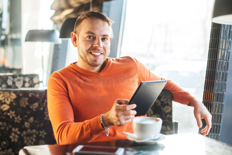 Handsome young man working with tablet, looking at camera, while enjoying coffee in cafe royalty free stock photography