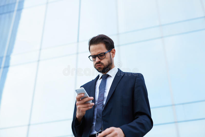Handsome young manager of a large corporation has received a message from the boss on a mobile phone. Despairing businessman reading text message while holding royalty free stock image