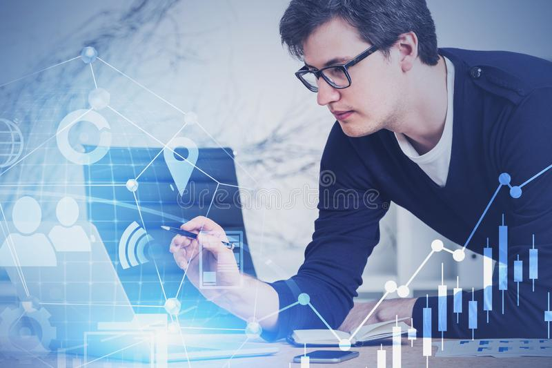 Handsome young market analyst working with chart. Young market analyst in casual clothes and glasses working with digital business interface in blurry office royalty free stock photos