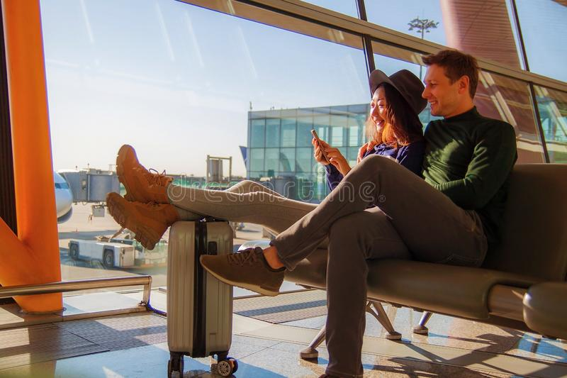 Portrait of happy couple using mobile phone at airport. Handsome young men and beautiful asian women  using mobile phone at airport near window, waiting for stock photos