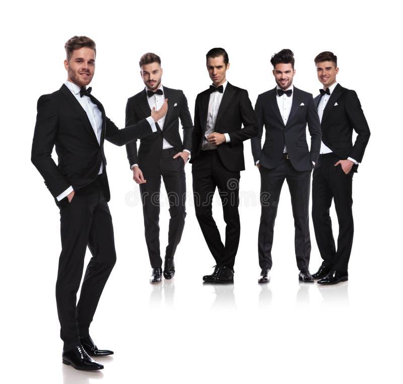 Handsome man in black tuxedo presents his elegant group stock photos