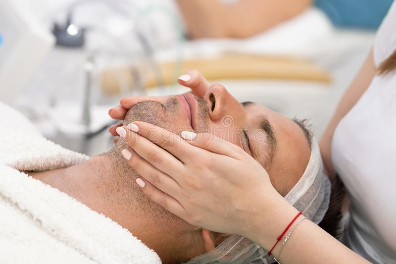 Young handsome man receiving facial massage and spa treatment. Handsome young men enjoying during facial massage in cosmetic salon, relaxing part of the skin stock photography