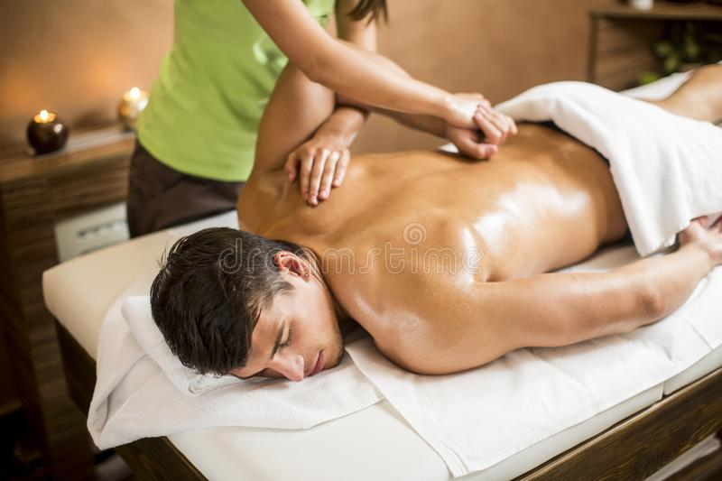 Young man having massage in spa royalty free stock photography