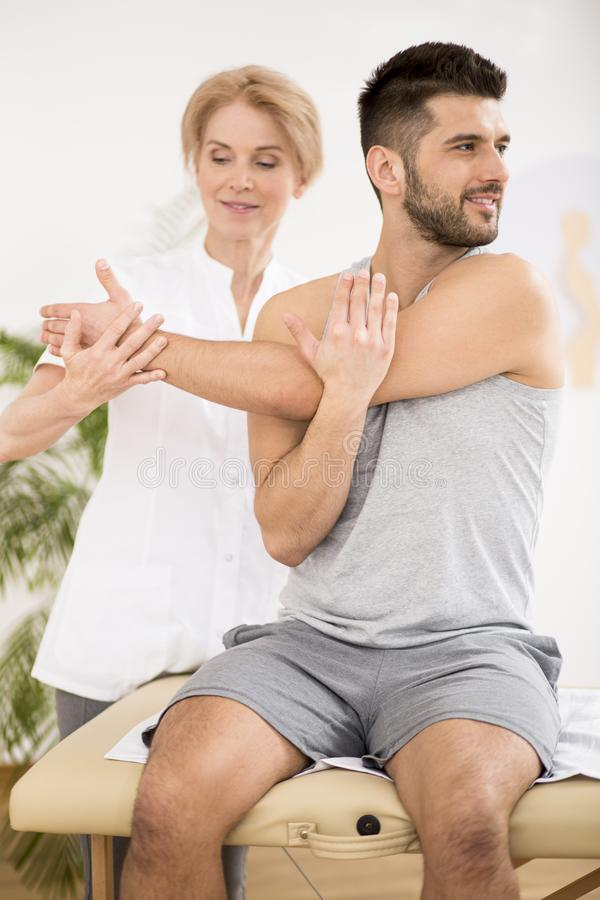 Handsome young man during physiotherapy session with professional doctor stock image