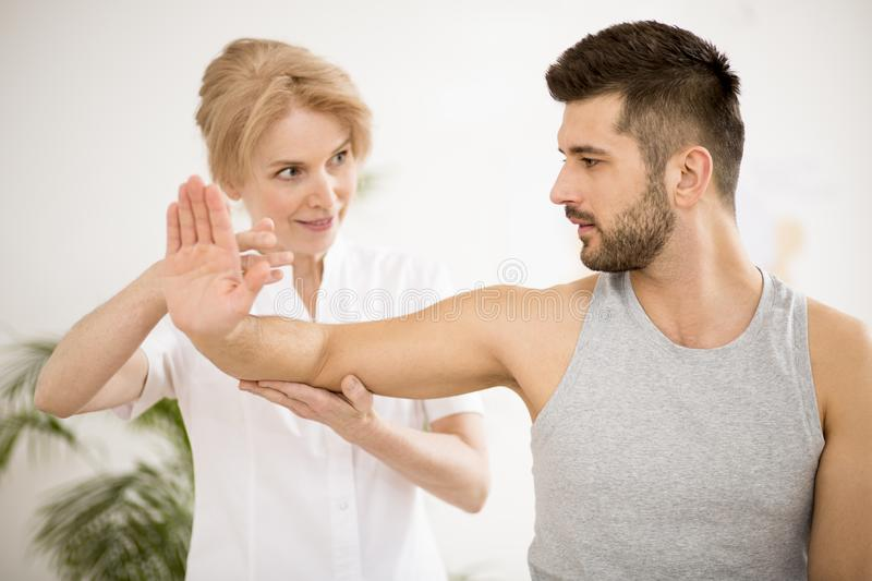 Handsome young man during physiotherapy session with professional doctor. Handsome young men during physiotherapy session with doctor stock photos