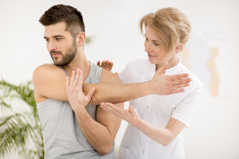 Handsome young man during physiotherapy session with professional doctor royalty free stock images