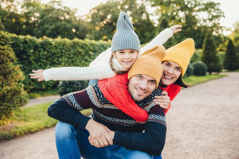 Handsome young man spends his free time with family, recieves embrace from adorable daughter and pretty wife, have picnic during a stock photography