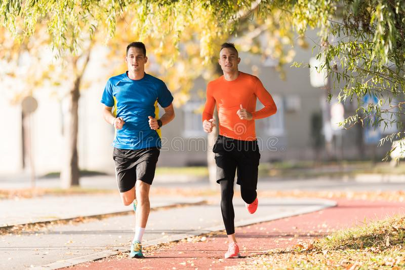 Handsome young men wearing sportswear and running at quay during. Autumn royalty free stock photo