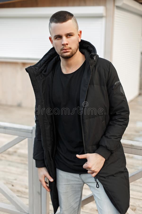 Handsome young models man in a trendy black winter jacket posing royalty free stock image