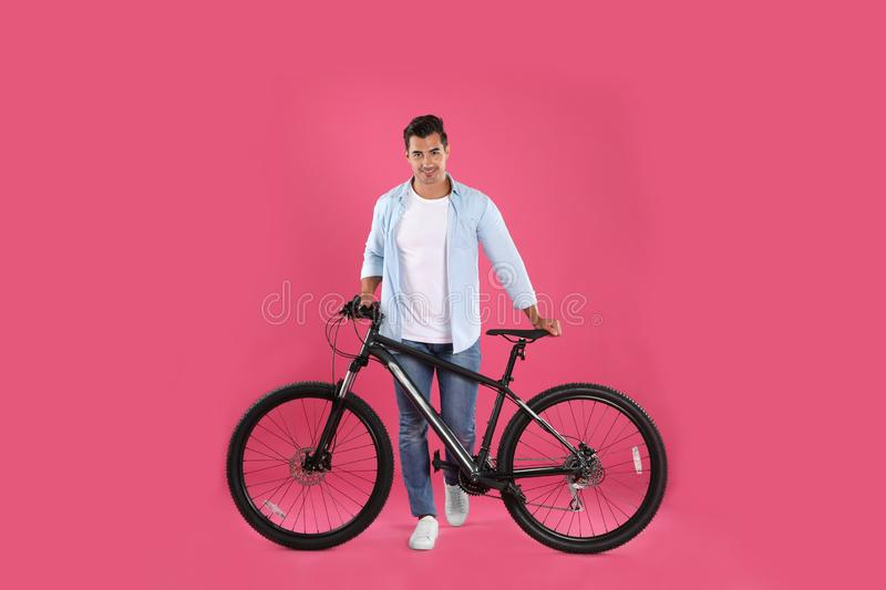 Handsome young  with modern bicycle on pink background stock images