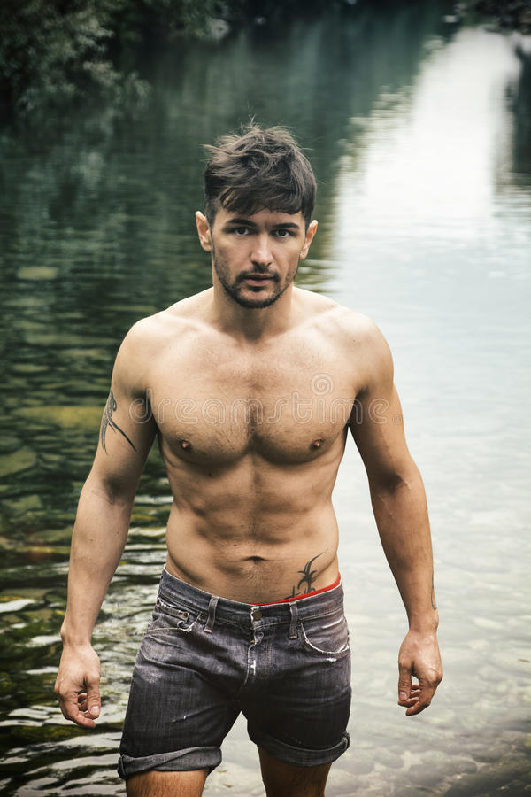 Young Man Next To River With Open Jacket On Naked Torso
