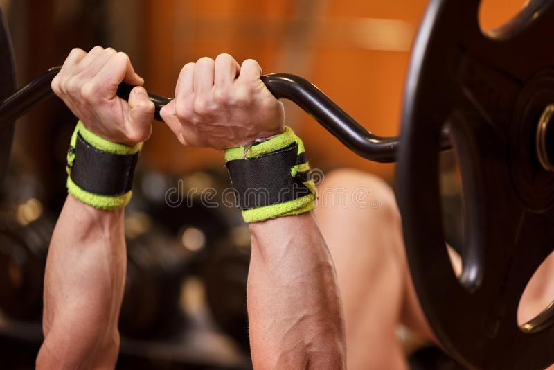 Handsome young muscular man close up, doing bench french press workout with barbell in gym. royalty free stock photography