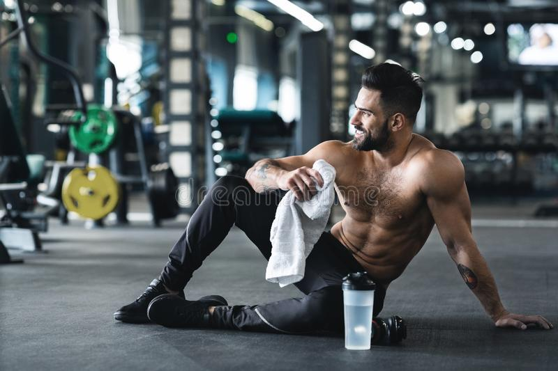 Handsome young muscular sportsman resting after workout royalty free stock photography