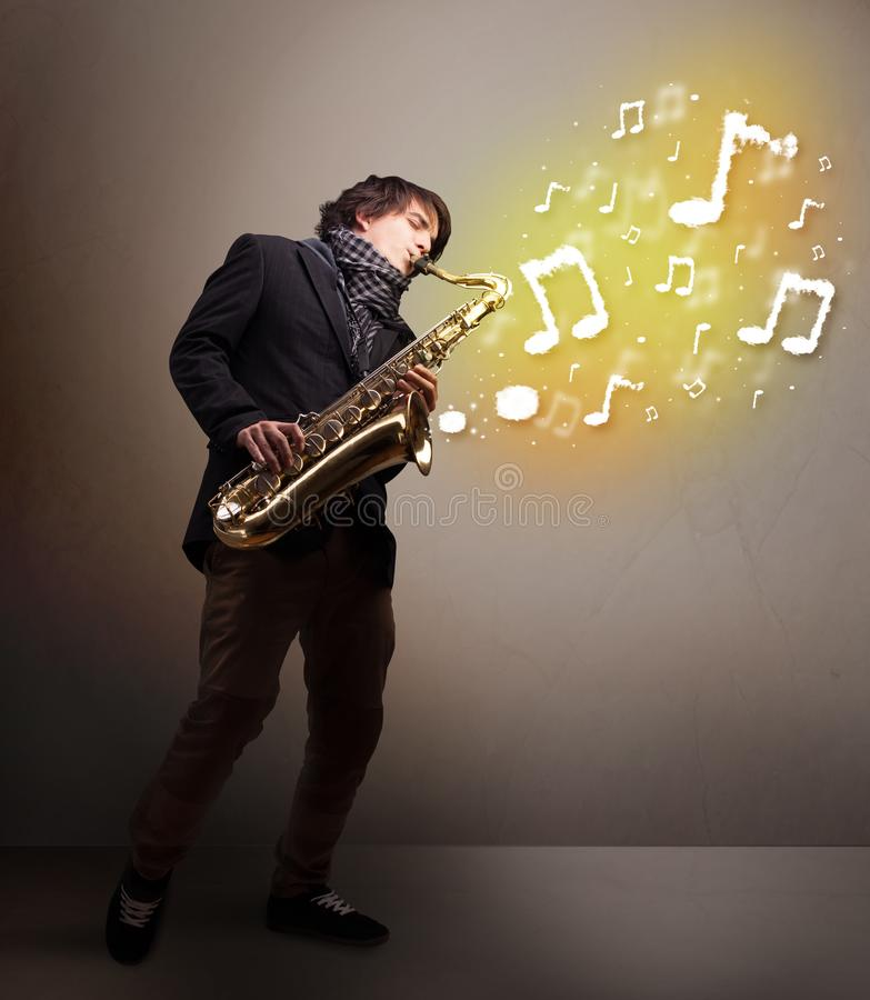 Handsome musician playing on saxophone with musical notes. Handsome young musician playing on saxophone with musical notes stock photo