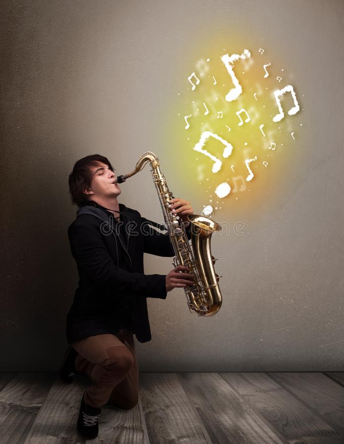 Handsome musician playing on saxophone with musical notes royalty free stock images