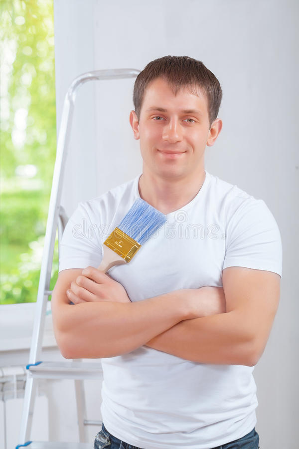 Handsome young painter with crossed arms looking at camera stock photo