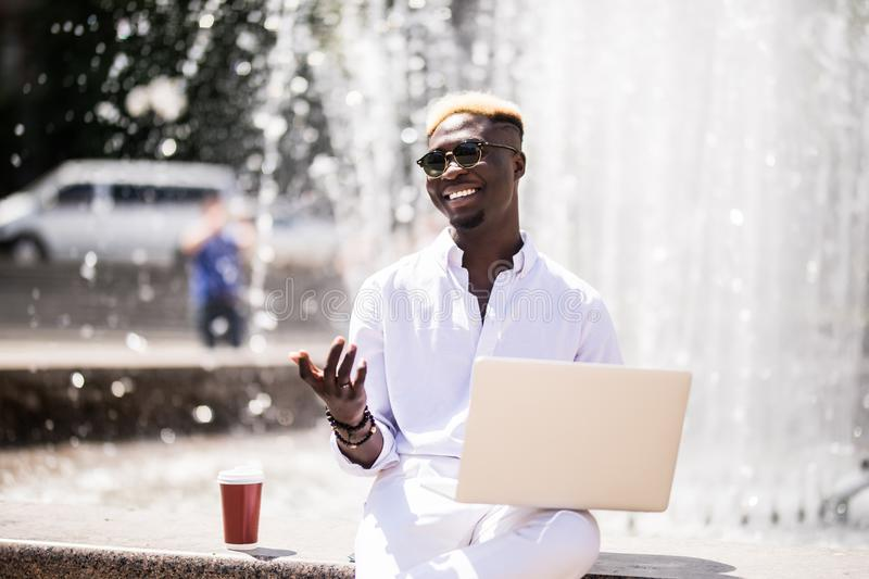 Handsome young pensive Afro American businessman is using a laptop while sitting outdoors in summer street near fountain at fresh royalty free stock images