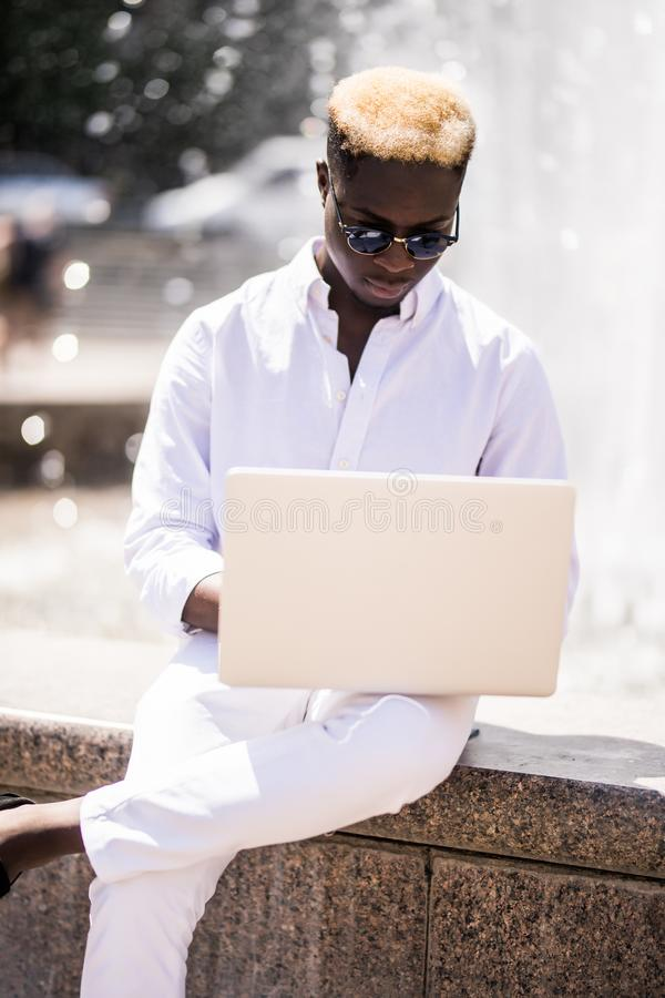 Handsome young pensive Afro American businessman is using a laptop while sitting outdoors in summer street near fountain at fresh stock photos