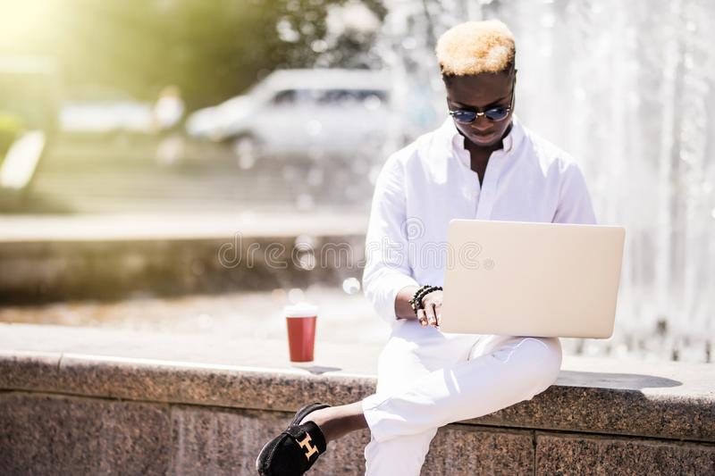 Handsome young pensive Afro American businessman is using a laptop while sitting outdoors in summer street near fountain at fresh royalty free stock image
