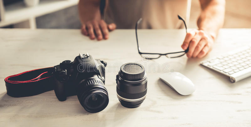 Handsome young photographer. Cropped image of handsome young photographer holding eyeglasses while working with computer in office royalty free stock image