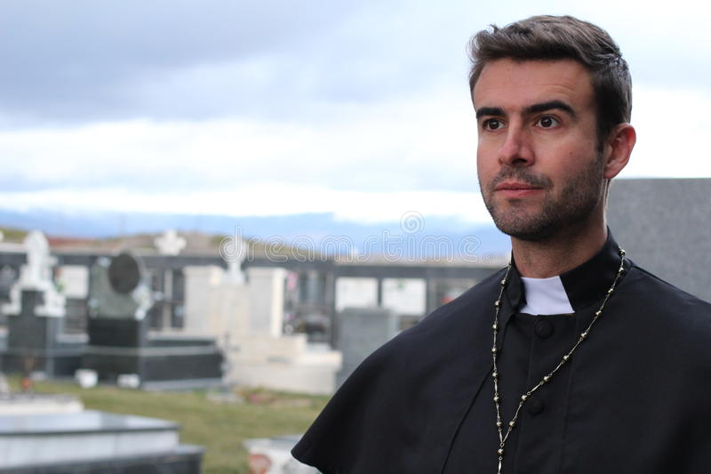 Handsome young priest close up looking away with copy space stock photography