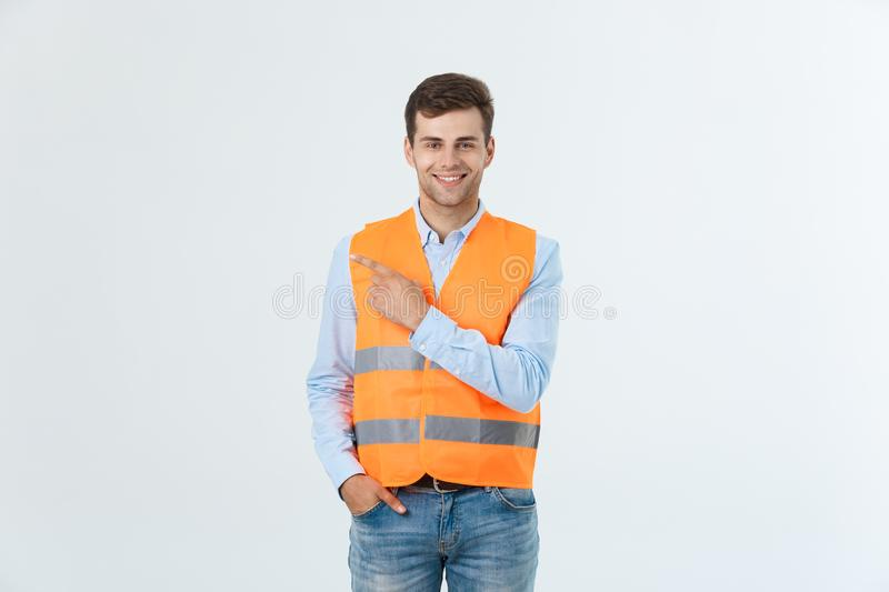 Handsome young professional engineer man over grey wall wearing orange vest amazed and surprised looking and pointing stock photos