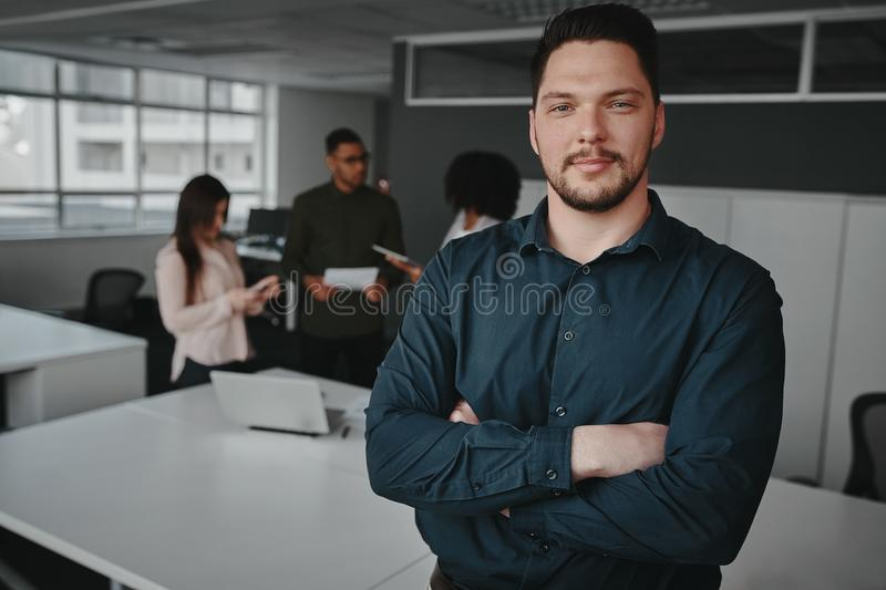 Handsome young professional man in office with folded arms looking at camera and other workers having conversation in stock images