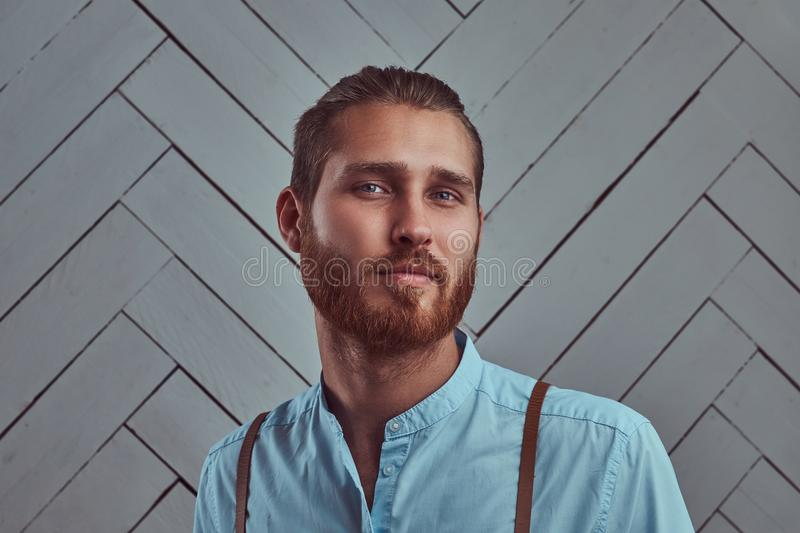 Handsome young retro stylish redhead man in suspenders posing against a white wall in a studio. stock photo
