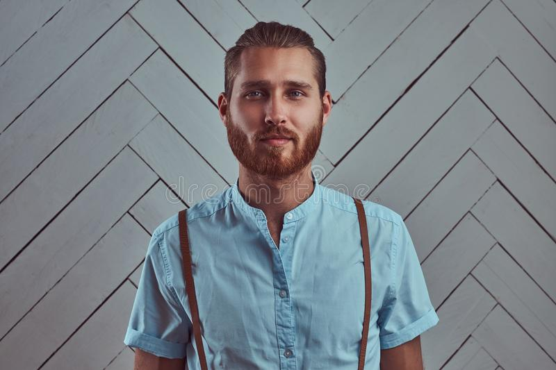 Handsome young retro stylish redhead man in suspenders posing against a white wall in a studio. royalty free stock photo