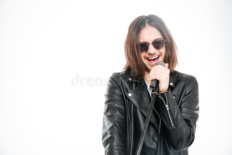 Handsome young rock singer in sunglasses singing into microphone stock photos
