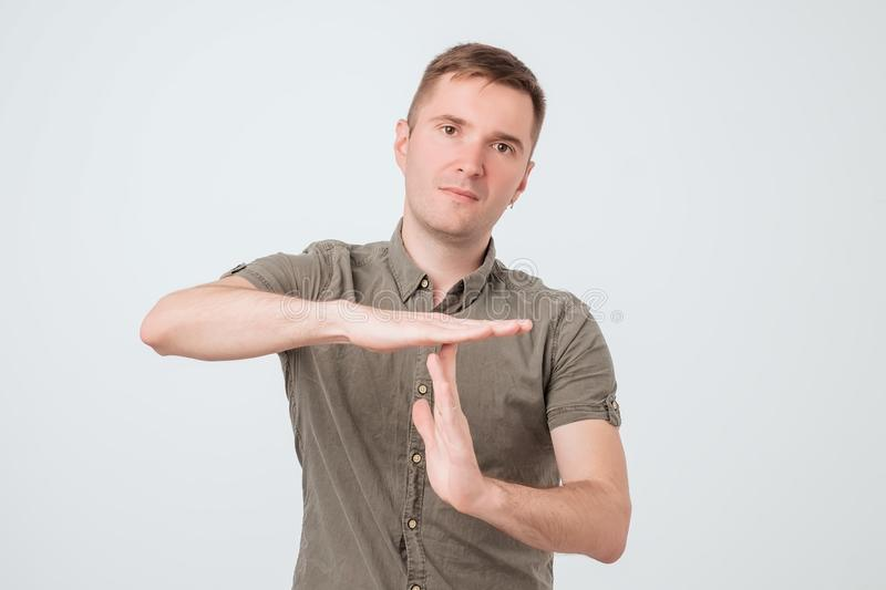 Handsome young serious man, coach showing time out gesture with hands, isolated on white background. stock photography