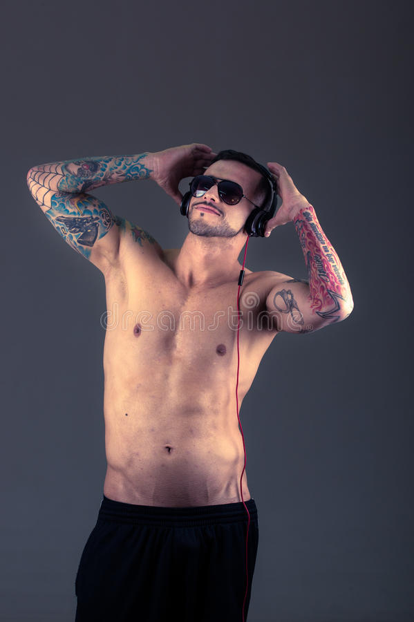 Handsome young shirtless tattooed man using stock images