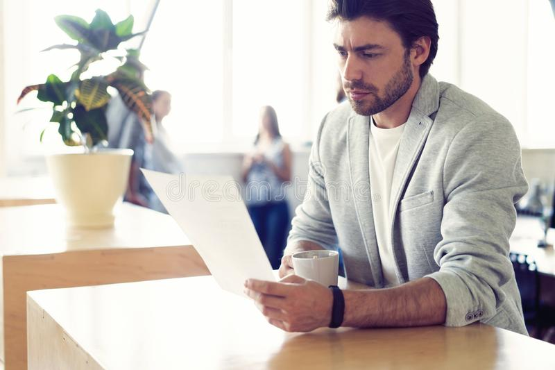 Handsome young smiling businessman working with documents. Handsome young smiling businessman working with documents in office royalty free stock image