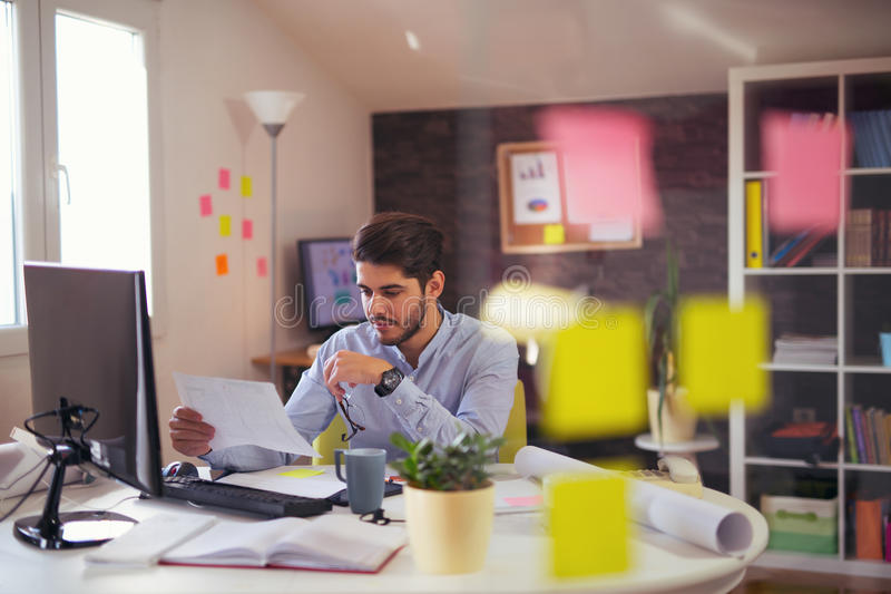 Handsome young smiling businessman working with documents stock photos