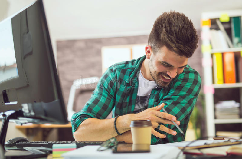 Handsome young smiling businessman working with documents. In office royalty free stock photo