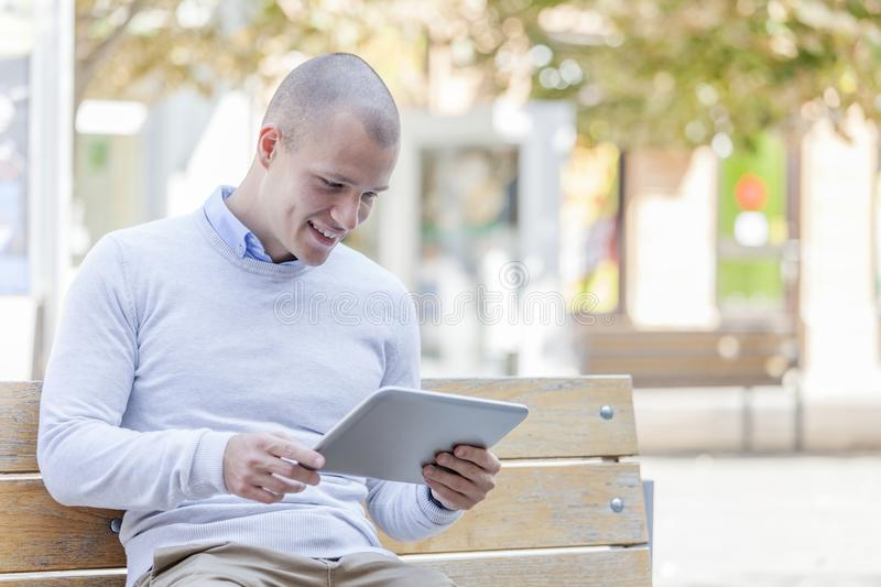 Handsome young smiling man, student uses digital tablet royalty free stock photos