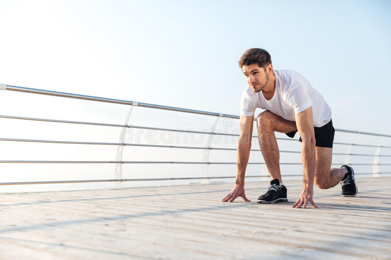 Handsome young sportsman preparing for start running. In the morning at sunrise royalty free stock photos