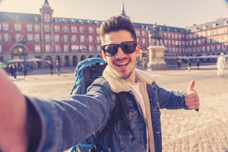 Handsome young student tourist man happy and excited taking a selfie in Madrid, Spain royalty free stock image