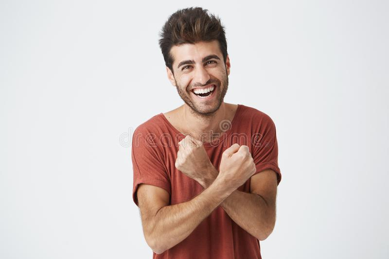 Handsome young sun-tanned man feeling excited, gesturing actively, keeping fists clenched and crossed, joyfully laughing royalty free stock photos