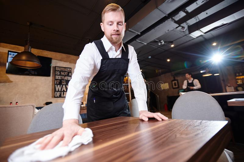 Handsome young waiter cleaning table in restaurant. Content handsome young waiter with beard wearing white shirt and apron standing at wooden table and cleaning stock images