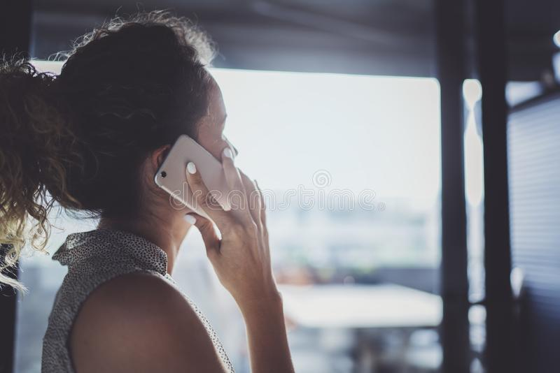 Handsome young woman talking with friends via modern smartphone while spending her time at modern urban cafe. royalty free stock photography