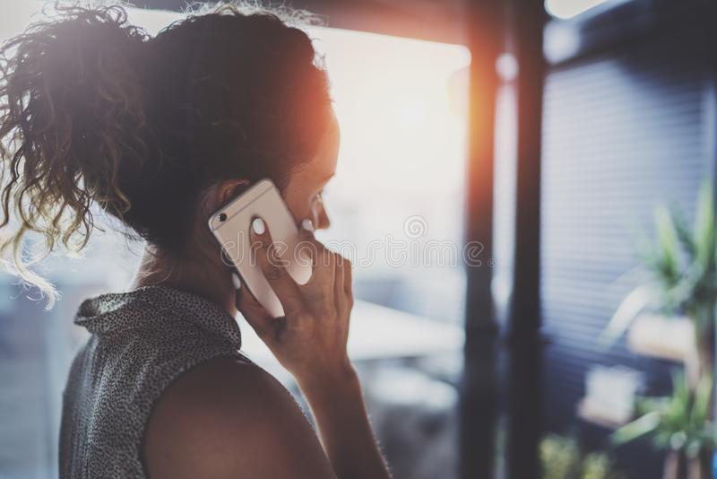 Handsome young woman talking with friends via modern smartphone while spending her time at modern urban cafe. royalty free stock image